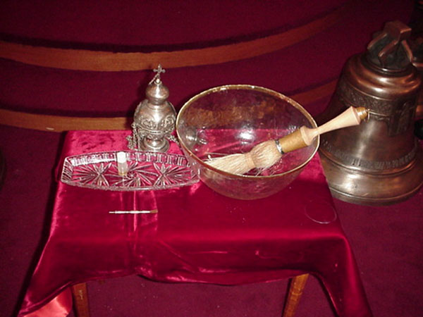 Table with Holy Water, Holy Chrism, and censer.